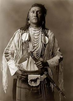 Holds Enemy, a Crow Indian Brave. It was created in 1908 by Edward S. Curtis.