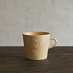 Designed by Oji Masanori and handcrafted at the Takahashi Kougei wood workshop in Hokkaido. The Kami mug is made of castor aralia wood from Hokkaido, shaped down to a thickness of 2 mm, which allows light to glow through but remains thick enough for durable insulation.