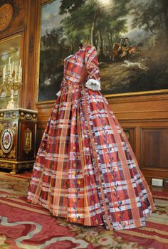 "Around 1784, fashionable ladies, including Marie Antoinette, took to wearing block-printed ribbons decorated with triangles evoking the horns, fangs, and claws of the newly ""discovered"" harpy. Isabelle de Borchgrave has given full reign to her imagination in the pattern emulating a taffeta with elements inspired by Scottish tartans interspersed with floral motifs. This dress is now on display in the Dining Room."