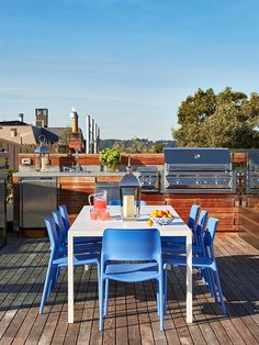 Rooftop patio with white table, blue chairs, and wood cabinetry around bbq