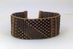 Beautiful African textile inspired loom woven beaded cuff made with brass, matte copper and matte black 11/0 glass seed beads, brass toggle bar