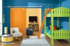 Dormitorio infantil con playroom integrado por una puerta corrediza de madera; paredes pintadas en azul, cama marinera verde y sillón individual.