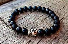 Pulseira de esferas negras de resina, com entremeio em metal na cor prata, em formato de Buda, confeccionada com fio de silicone.    Ao comprar, por favor informar o tamanho da pulseira. R$ 22,90