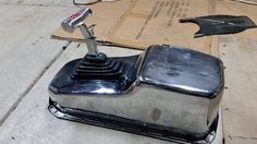 and over turned chrome oil pan as a shifter cover for a B&M shifter.