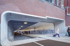 A 361-foot path called Cuyperspassagerecently opened in Amsterdam as a way for pedestrians and cyclists to travel from the city center to the IJ waterfront. Now, 15,000 daily commuters not only have dedicated road space, but a fantastic mural to look at as they walk or ride from one destination to the next. Cuyperspassage was constructed by Benthem Crouweland features two sides that separate the pedestrians from the cyclists. The darker bike lane has sound-absorbing asphalt and steel…