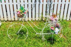 Skurrilen weiß Fahrrad-Skulptur mit Topflappen Blume.
