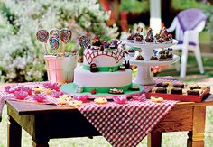 Festa de criança - A mesa principal é a estrela, cheia de doces como brigadeiros, bichos-de-pé, quadradinhos de bolos de limão e de chocolate, minicupcakes e pirulitos espetados em uma cesta repleta de balas. O bolo leva miniaturas que representam um piquenique, tema da festa