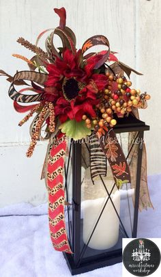This is a fall floral lantern swag with burlap and printed ribbons, a large red sunflower, pumpkins and berries. This swag attaches to your