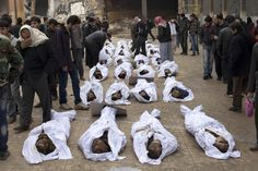 Men search for their relatives amongst the bodies of Syrian civilians executed and dumped in the Quweiq river, in the grounds of the courtyard of the Yarmouk School, in the Bustan al-Qasr district of Aleppo on January 30, 2013. AFP PHOTO/JM LOPEZ