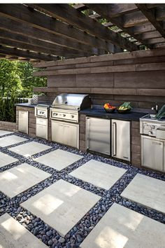 Looking for a an outdoor kitchen idea? For this landscape project, the Borealis wall was used for the back wall and the island, which includes an outdoor grill, a small fridge and other home appliances made for outdoor living. The Travertina Raw slabs wer #outdoorkitchengrillideas #outdoorkitchengrillhome