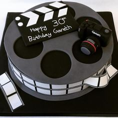 Videographer themed birthday cake. Film reel with Canon camera and clapper board. Bespoke cakes handmade by A Taste of Wonderland. #Videographer #Cake
