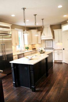 White cabinets, dark island, white countertops, dark wood floor, pendant light over island