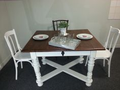 A beautiful brown/white dining table with 2 brown and two white chairs