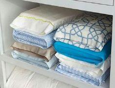 Ropa de cama metida en fundas de almohada para ordenar bien el armario