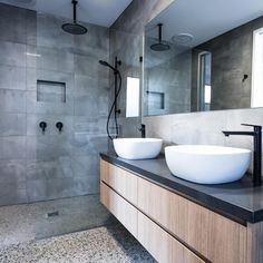 Concrete tiled walls with matte black rainfall shower head, matte black wall shower mixer, matte black rail shower. Timber wall hung vanity with dark grey concrete top. Twin top mounted vessels with matte black vessel mixers. Concrete Bathroom, Wooden Bathroom, Bathroom Faucets, Small Bathroom, Bathroom Ideas, Bathroom Mirrors, Grey Bathroom Wall Tiles, Polished Concrete Kitchen, Concrete Shower
