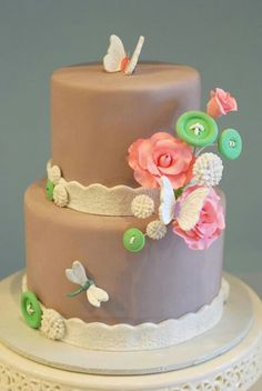 Do as pink & lace border cake with flowers and buttons and butterflies. One butterfly each for Mom, Dad & Shari.   Cute as a button written on a banner on top or along the cake round at the bottom
