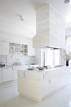 Gwyneth Paltrow's New York City apartment is the ultimate is feminine, white kitchens. Chrome taps and accessories add a touch of the industrial while the white washed timber floors make it light and bright. The range hood shows a different way of using marble in the kitchen, on subway-style tiles instead of one large slab.