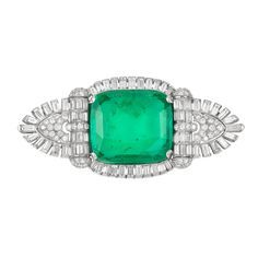 Art Deco Platinum, Emerald and Diamond Brooch   The modified shield-shaped brooch centering one cushion-shaped emerald approximately 24.00 cts., edged and flanked by 62 round and 68 baguette diamonds approximately 6.40 cts., circa 1930,