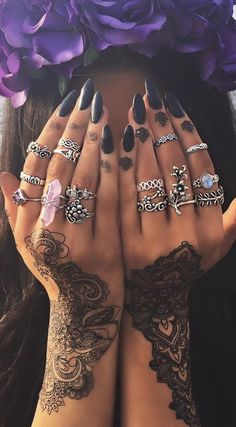 Black nails with boho rings and henna tattoo