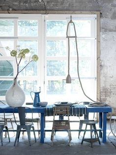 Blauwe extreem lange eettafel. Verschillende stoelen geven het een speels effect. Stoelen wel allemaal in dezelfde kleur om een eenheid binnen de chaos te creëren.