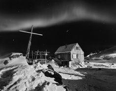 The Northern Lights glow above Tinnittaqilaq village.    Photo: Ragnar Axelsson