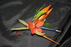 Beautiful Tropical boutonniere made with orange Mokara Orchid and Bird of Paradise