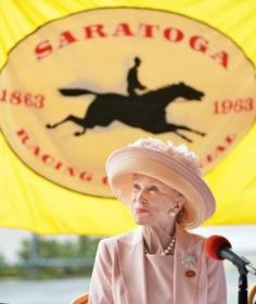 Marylou Whitney's accomplishments, awards, & good deeds are both truly impressive & extensive! Part of the reason people look forward to raceday, The Whitney, is the fashion. Much of the fashion & style on this day we attribute to Ms. Marylou herself. Never have you seen Marylou disheveled. Her style is always impeccable, elegant, & classic. She wears hats to the races (as every woman should) with bold statement jewelry. Pearls are her go-to & she has created quite the staple in wearing…