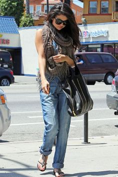 Selena Gomez wears her dungarees en route to the gym - the knitted scarf and flat sandals give it an off-duty edge.