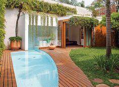 A piscina revestida de pastilhas brancas tem forma orgânica e entra na sauna, fechada por painéis de vidro. Projeto do arquiteto Jorge Siemsen.