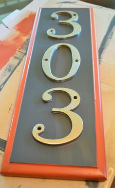 Cute idea-old cabinet door repainted and screw house numbers onto it