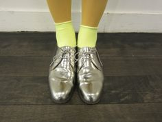 Super cool! Neon socks over mustard tights PLUS metallic shoes :)
