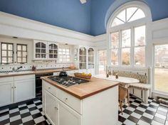 Blue ceiling, checkerboard floor, white cabinets, butcherblock countertops, banquette... nice kitchen!!!