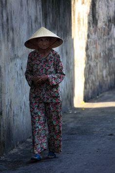 Hoi An Alley | An elderly woman walking down a narrow side street in Hoi An ,Viet Nam