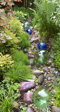 Love these glass floats! The rock-lined swale is both design feature and effective rain garden. It soaks up runoff in this wet, steep-slope garden. Glass floats further the look of a dry streambed. Rain Garden Design, Garden Art, Garden Pond, Glass Garden, Water Garden, Shade Garden, Garden Spheres, Pond Landscaping, Landscaping With Rocks