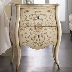 Beige bombe chest with a hand-painted floral motif.Product: Accent chest    Construction Material: Wood    Color: Beige    Features: Two drawersHand-painted floral motif              Dimensions: 29 H x 24 W x 16 D