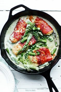 Prosciutto wrapped chicken fillet with asparagus and pesto sauce, written in Russian.