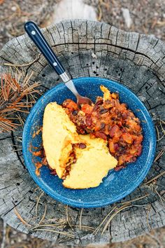 Chili and cornbread in a blue camping bowl on a stump.