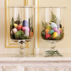 glass containers filled with colorful Easter eggs and fern leaves