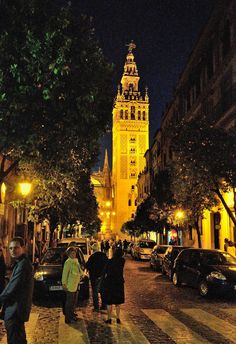 """La Giralda, view from  : Calle Mateos Gago -------------------------------------------- La Giralda : It is the symbol of Seville.  It was built in 1198 at the request of the Almohad caliph Abu Yusuf Yaqub al-Mansur to be the minaret of the mosque called Dhem Mukyarriml.  The Giralda is the same as the other two minarets: the Hassan Tower in Rabat and the Kutubiyya (Koutoubia) in Marrakech. These three towers are the group of """"Three Sisters"""".  The total height of the Giralda from the…"""