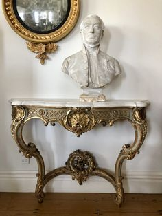 A French carved gilt-wood and grey lacquered table in the style of Louis XV with a shaped white Carrara marble top. The frieze has a carved gilt-wood shell and lattice work, cabriole legs, joined by a stretcher with an addorsed 'C' scroll foliate decoration beneath. Soft grey painted accents.  Pictured with: Antique plaster bust of a gentleman in uniform English Regency gilt wood convex mirror c.1820 Dimensions:  H920 x W1290 x D450mm  Code: 24EA16