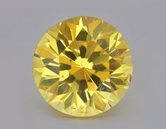 Nearly 24 carats of unheated vivid yellow sapphire remarkably cut in a round brilliant style.