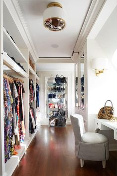 A Large walk-in closet is every girl dream, especially when accompanied with lucite shelving unit displaying designer handbags.