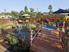 Country French Inspired Formerly a barren lot strewn with broken concrete, this backyard in La Mesa, Calif. received a complete makeover that included a privacy fence, pond and three distinct hardscape areas. A redwood bridge connects the spaces and helps add to the rural feel.