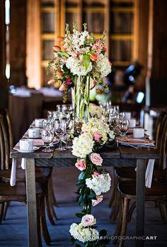 Brides.com: . A cascading runner with white hydrangeas and peach roses offsets a single pillar centerpiece.