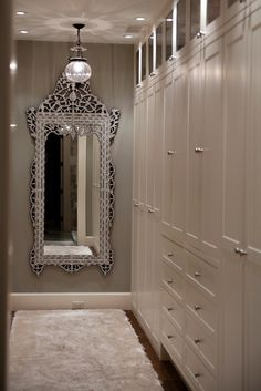 Glamorous walk-in closet with Venetian floor mirror, gray walls paint color and white floor to ceiling built-in cabinets.