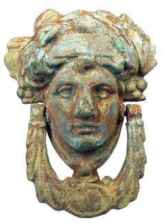 Ancient Roman. Bronze door knocker of a female muse or Goddess with upswept hairstyle, the knocker suspending from her ears. Vivid green patina and earthen encrustations. 100 BC