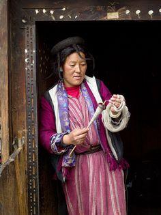 Bhutan - The Brokpa - A Brokpa woman spinning sheep wool using a drop spindle known as a Yoekpa