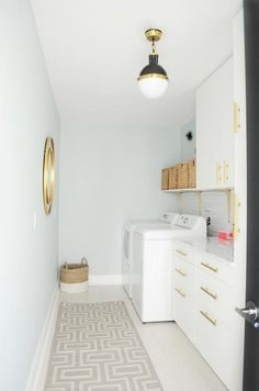 Laundry Room Design: Simple white and gold laundry room, featuring ligh...
