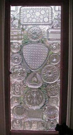 glass window with plates, lids and flat marbles glued to the surface - awesome!