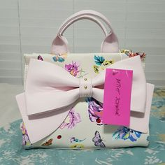 NWT Betsey Johnson pink bow floral purse handbag Absolutely gorgeous bag by Betsey. Comes with a shoulder strap. Accents are gold and pale, pastel pink; pattern features flowers, butterflies, and ladybugs. Midsized bag, two inner compartments and an inner zipper pocket, and a back zipper pocket. Cute for any occasion! Betsey Johnson Bags